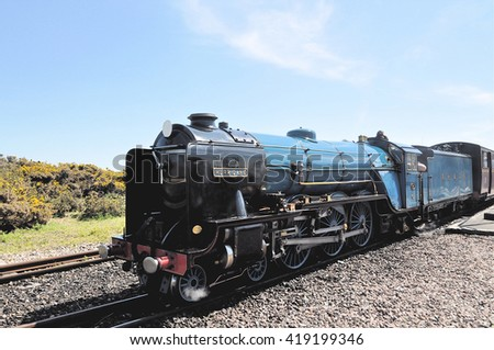 HYTHE, UK - MAY 8, 2016. The original 1926 one third scale steam locomotive on the 15 inch narrow gauge railway completed in 1928 from Hythe to Dungeness in Kent, southern England, UK. - stock photo