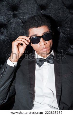 I am a boss here! Fashionable young Afro-American man sitting on the chair holding hand on glasses  - stock photo