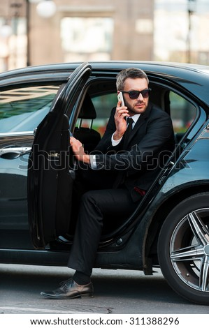 I am already here. Confident young businessman talking on the mobile phone while coming out of his car - stock photo