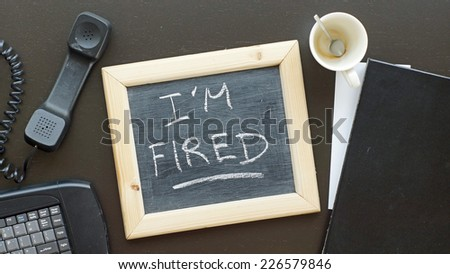 I am fired written on a chalkboard at the office - stock photo