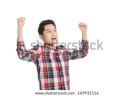 I am happy! Smiling Chinese teenage boy keeping arms raised while standing isolated on white - stock photo