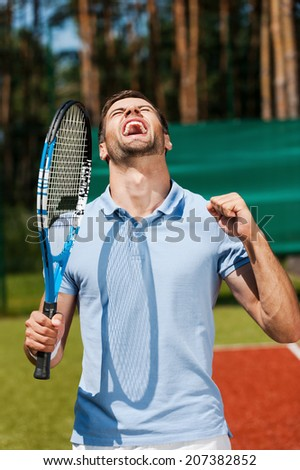 I am the best! Happy young man in polo shirt holding tennis racket and gesturing while standing on tennis court  - stock photo