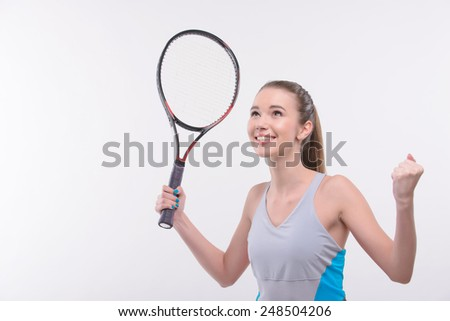 I am the winner. Rear view of beautiful happy young woman in sports clothes holding tennis racket and raising hands  while standing against white background - stock photo