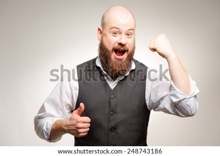 I am winner! Happy young man looking at camera and gesturing while standing isolated on studio background - stock photo