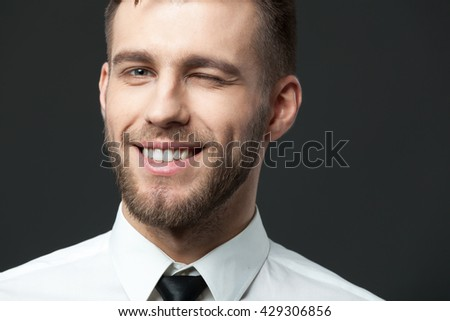 I am young and successful! Studio portrait of handsome young businessman smiling and winking. - stock photo