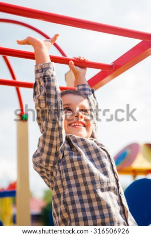 I can do it! Playful little boy expressing positivity while having fun on jungle gym - stock photo