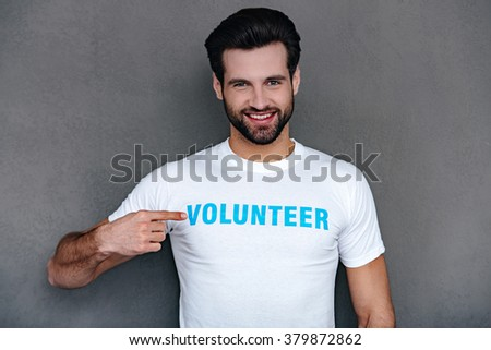 I can help you! Confident young man pointing at volunteer title on his t-shirtand looking at camera with smile while standing against grey background