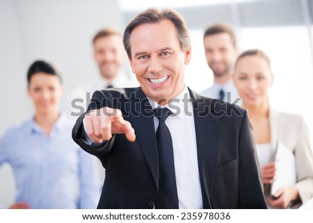 I choose you! Confident mature businessman pointing you and smiling while his colleagues standing in the background  - stock photo