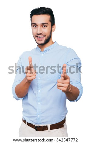 I choose you! Confident young Indian man pointing you and smiling while standing against white background - stock photo