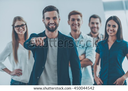 I choose you for my team! Handsome young man pointing you and smiling while group of happy young people standing on background  - stock photo