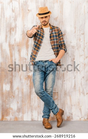 I choose you! Full length of handsome young man looking and pointing at camera while standing against the wooden wall  - stock photo