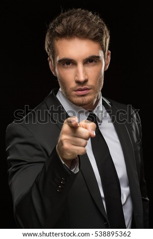I choose you. Vertical studio shot of a handsome young businessman in a suit pointing at the camera with his finger on black background