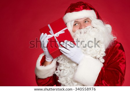 I feel Christmas specials. Santa holding a present box to his ear and listening carefully  - stock photo