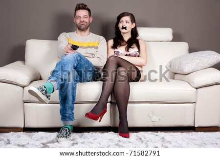 I finally managed to shut her up! Young woman with taped mouth sitting beside her boyfriend/husband who's enjoying in silence and watching TV. - stock photo