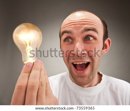 I have an idea! Surprised man holding lighting bulb - stock photo