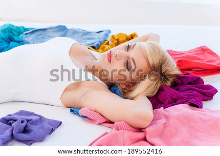 I have nothing to wear! Depressed young blond hair woman lying on the bed with clothes laying all around her and looking away - stock photo