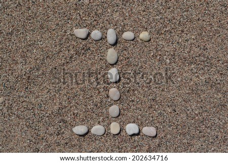 I letter made of stones on sand  - stock photo