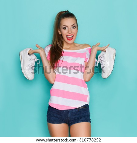 I Like Comfortable Sneakers. Shouting young woman in pink striped shirt and jeans shorts standing with arms raised and holding white sports shoes. Three quarter length studio shot on teal background. - stock photo