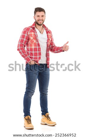 I like it. Smiling young man in jeans and lumberjack shirt showing thumb up. Full length studio shot isolated on white. - stock photo
