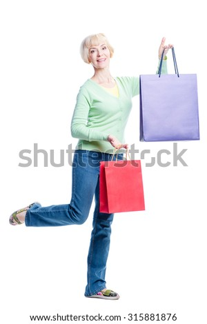 I like shopping! Happy middle aged woman  holding shopping bags. Isolated on white background - stock photo