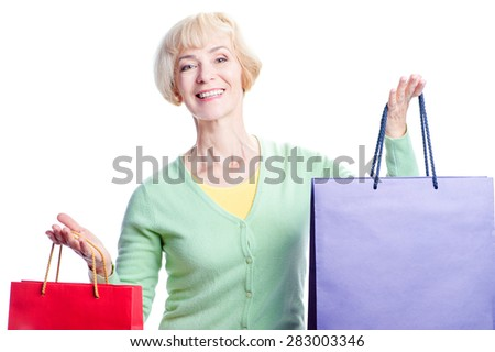 I like shopping! Happy middle aged woman  holding shopping bags while standing isolated on white background - stock photo