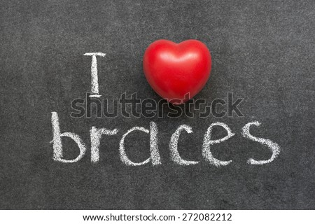 I love braces phrase handwritten on chalkboard with red heart symbol  - stock photo