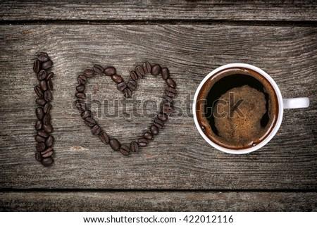 I love coffee, coffee beans and mug on wood background - stock photo