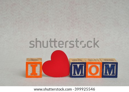 I love mom spelled with colorful alphabet blocks and a red heart isolated on white background - Mothers Day - stock photo