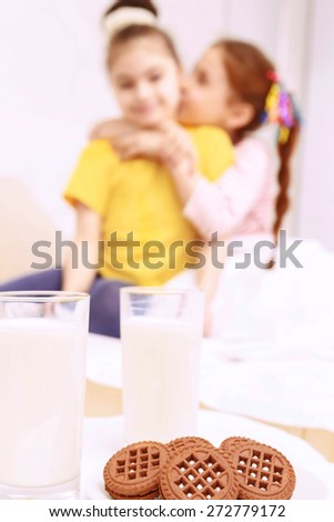 I love my friend. Two young nice girls standing behind cookies and milk and hugging. - stock photo