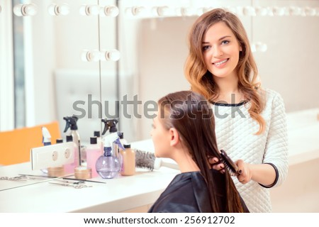 I love my job. Beautiful hairdresser doing hairstyle to her client and smiling at camera while standing on the background of a professional hairdressing salon - stock photo