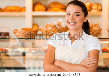 I love my job! Beautiful young woman in apron keeping arms crossed while standing in bakery shop - stock photo