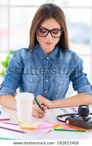I love my job! Cheerful young businesswoman in casual wear writing something in note pad while sitting at his working place - stock photo