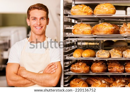 I love my job! Handsome young baker in apron keeping arms crossed and smiling while leaning at the tray with fresh baked bread  - stock photo