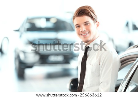 I love my job. Portrait of a handsome young car sales man in formalwear leaning at car and looking at camera in a car dealership  - stock photo