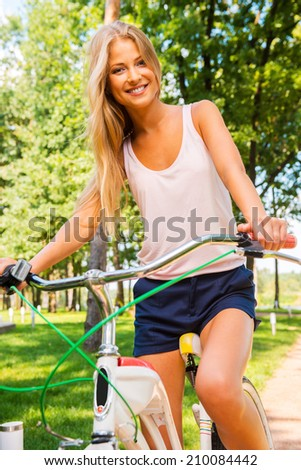 I love my new bike! Beautiful young blond hair woman smiling and looking at you while riding her bicycle outdoors  - stock photo