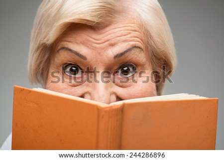 I love reading. Closeup of smiling senior woman holding orange book hiding her face behind it while standing against grey background - stock photo