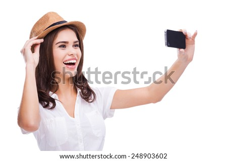 I love selfie! Cheerful young woman in funky hat making selfie with her smart phone and smiling while standing against white background - stock photo