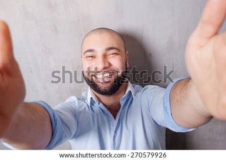 I love selfie! Handsome young latino man in shirt holding camera and making selfie and smiling while standing against grey wall. - stock photo