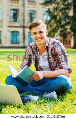 I love studying. Cheerful male student reading book and smiling while sitting on the grass and in front of university building