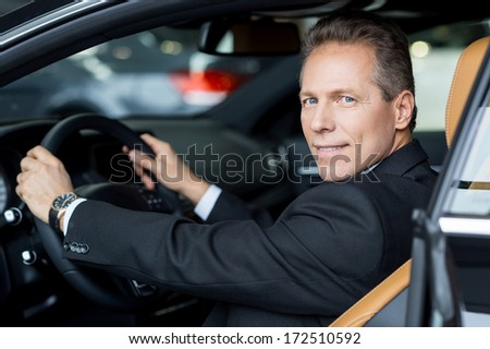 I love this car. Side view of cheerful senior man in formalwear sitting in car and looking over shoulder - stock photo