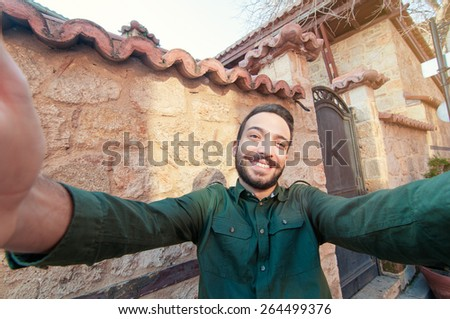 I love travel! Handsome young man in shirt holding camera and making selfie and smiling while standing against old town background - stock photo