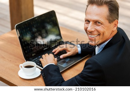 I love working outdoors. Top view of cheerful mature man in formalwear working on laptop and smiling while sitting in outdoors cafe - stock photo