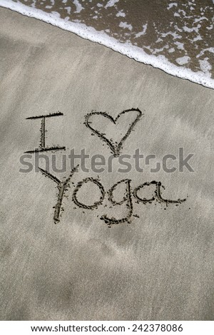 I love yoga, a message written in the sand at the beach. - stock photo
