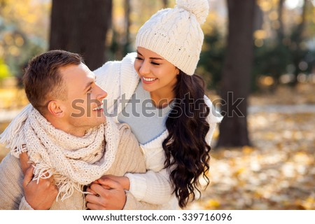 I love you. Beautiful young loving couple is embracing in the autumn park. The man is sitting and looking at his girlfriend happily. The woman is standing and smiling - stock photo