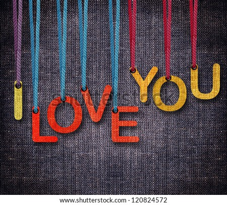 I love you hanging by rope as puppeteer on sackcloth background. - stock photo