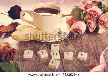 I love you made of letter cubes ,dried roses ,cup of coffee and heart shaped cookies with sugar for valentine on wooden table in vintage style - stock photo