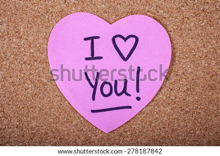 I Love You message written on a piece of heart-shaped note paper. - stock photo