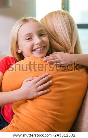 I love you mom! Happy mother and daughter hugging while sitting on the couch together  - stock photo