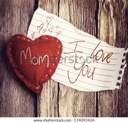 I Love You Mom written on a peace of paper and a heart on a wooden background, with retro filter effect - stock photo