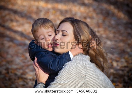 I love you mom, young mother with her little  son in hug, autumn day in park, closeup - stock photo